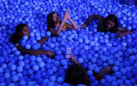 Friends enjoy a ball pit and pose for a photo together.