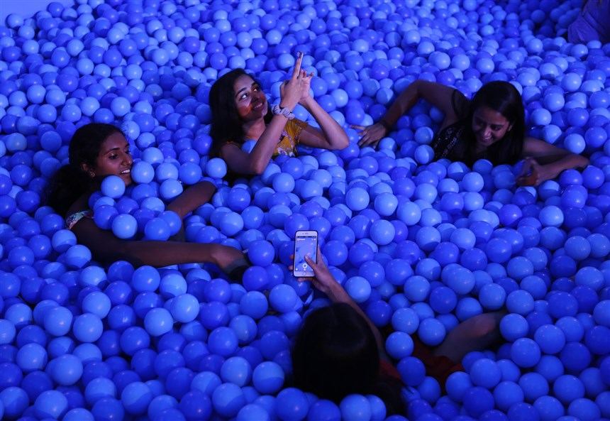 Friends+enjoy+a+ball+pit+and+pose+for+a+photo+together.